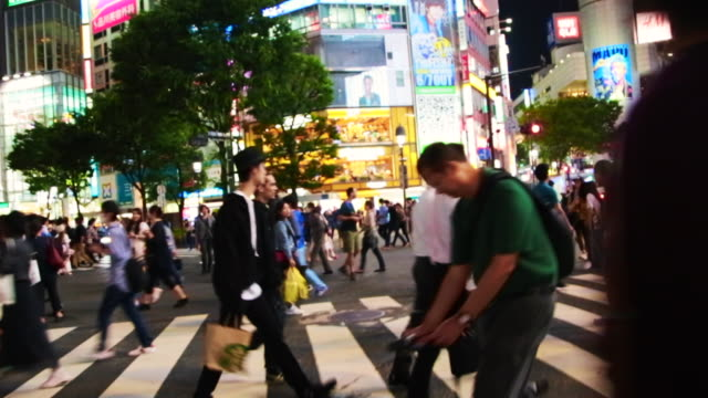 time lapse of the bustling pedestrian crossing in shibuya with people and cars during work day at night. - 商業地域点の映像素材/bロール