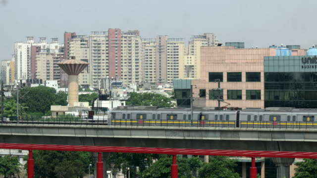 time lapse of the delhi metro train passing by on an elevated corridor with highrise buildings in the background - non urban scene stock-videos und b-roll-filmmaterial