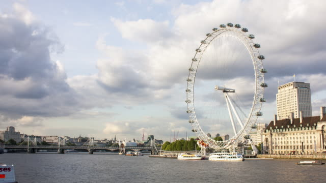 "4k time lapse of the ""london eye"" spinning on the thames river - overcast stock videos & royalty-free footage"