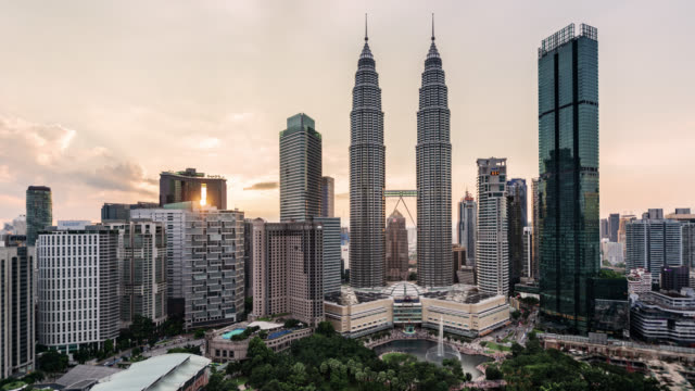 tl/ time lapse of the petronas towers and kuala lumpur skyline at sunset - petronas twin towers stock-videos und b-roll-filmmaterial