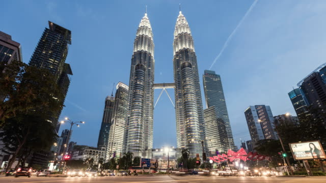 time lapse of the petronas towers with passing traffic in foreground - kuala lumpur stock videos & royalty-free footage