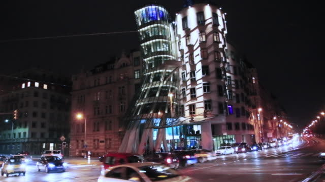 time lapse of the prague city at night with intersection and busy traffic in the dancing building a local landmark in prague. - local landmark stock videos and b-roll footage