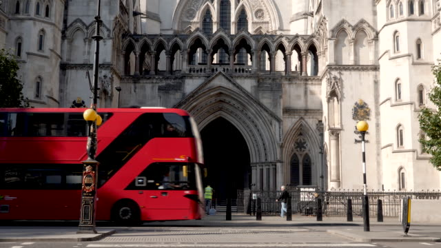 time lapse of the royal courts of justice in london, england, uk. entrance shot with red buses and black taxi cabs passing by on the street. - column stock videos & royalty-free footage