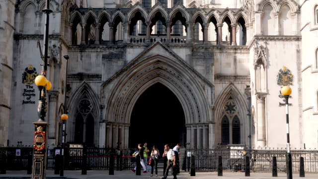 time lapse of the royal courts of justice in london, england, uk. entrance shot with black taxi cabs passing by on the street. - justice concept stock videos & royalty-free footage