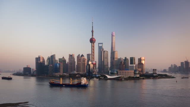 tl/ time lapse of the shanghai skyline, cargo ships on the pudong river passing by the financial district - shanghai tower stock videos & royalty-free footage