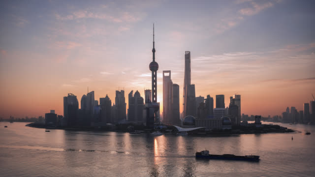 tl/ time lapse of the shanghai skyline, cargo ships on the pudong river passing by the financial district at sunrise - global economy stock videos & royalty-free footage
