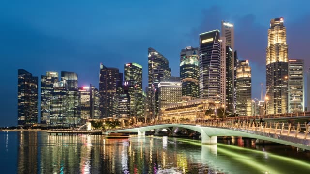 time lapse of the singapore skyline and financial district at dusk, with a pedestrian footbridge in the foreground - martin luther: his life and time stock videos & royalty-free footage