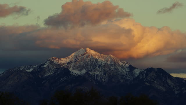 time lapse of the snowcapped wasatch mountains above salt lake city, ut at sunrise/sunset with a dramatic cloudscape - utah stock videos & royalty-free footage