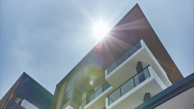 time lapse of the sun behind a modern building - flat stock videos & royalty-free footage