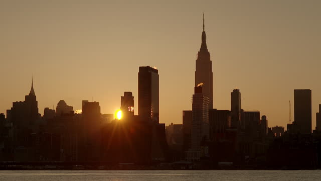 Time Lapse of the sun rising through the buildings in Midtown Manhattan early morning on the Hudson River.