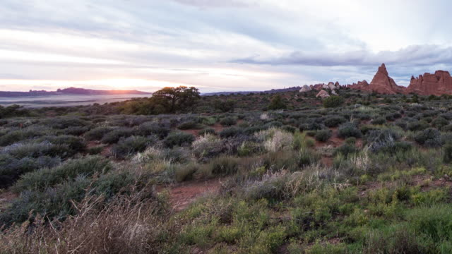 A time lapse of the sun setting in Moab, Utah, featuring scrubland in the foreground with low hanging clouds moving across the sky.