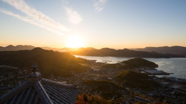 vidéos et rushes de laps de temps du soleil couchant sur un village de pêcheurs sur la côte - hiroshima prefecture