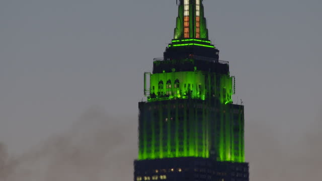 time lapse of the tower of the empire states building is illumined with green.  the green lights  change color.  a wave a heat distortion blurs the image. - st. patrick's day stock videos & royalty-free footage