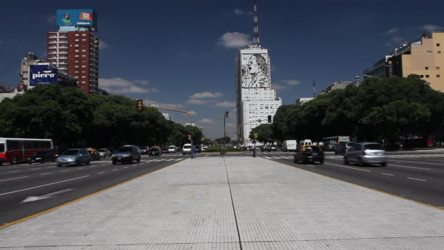 time lapse of the traffic at the street july 9 avenue. its name honors argentina's independence day, july 9, 1816. a sign of evita can be seen in the... - street name sign stock videos & royalty-free footage