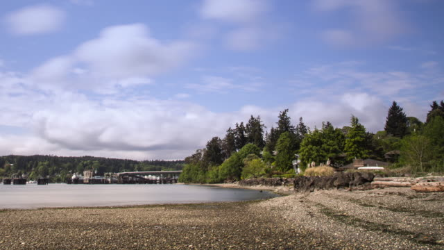 W/S time lapse of the Washington State Ferry Terminal at Eagle Harbor on Bainbridge Island on a sunny summer day with low clouds