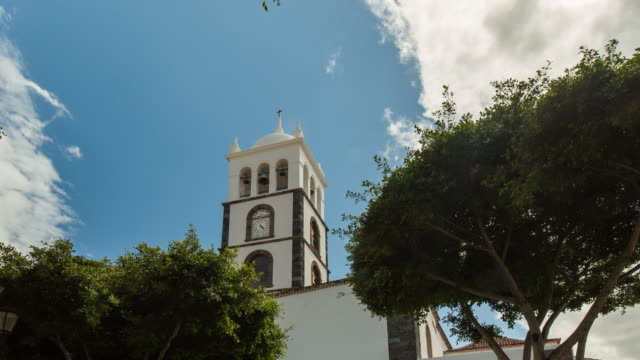 4K Time lapse of the watch tower of the Garachico church with clouds and trees, Tenerife, Spain
