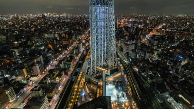 4k zeitraffer von tokyo skytree cityscape mit verschiedenen gebäudehochkratper und verkehrsstraßenkreuzung in stoßzeiten in der nacht in tokio, japan. japanische kultur und verkehrskonzept - steel stock-videos und b-roll-filmmaterial