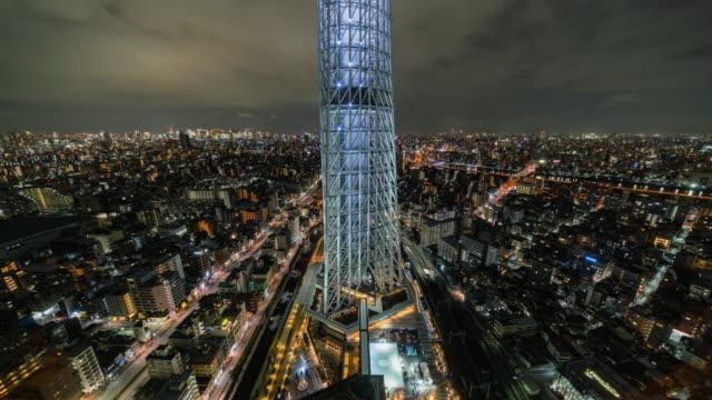 4k zeitraffer von tokyo skytree cityscape mit verschiedenen gebäude wolkenkratzer und verkehrsstraßen kreuzung in der hauptverkehrszeit in der nacht in tokio, japan. japanisches kultur- und transportkonzept - steel stock-videos und b-roll-filmmaterial