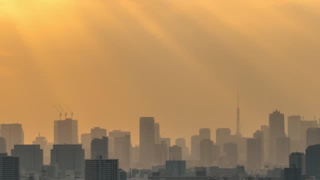 4k zeitraffer von tokyo skytree mit verschiedenen gebäuden stadtbild zum sonnenuntergang, die sonnenstrahlen haben von tower hall funabori observation tower, japan - in silhouette stock-videos und b-roll-filmmaterial