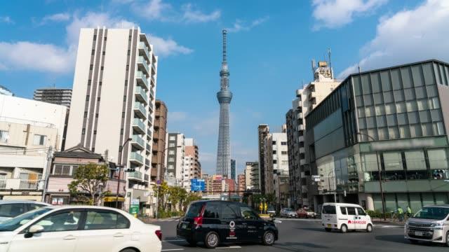 東京スカイツリーの4k タイムラプスは、東京市のラッシュアワーにおける様々な建物の街並みと交通道路の交差点で位置しています。日本の文化と超高層ビルのコンセプト - スカイツリー点の映像素材/bロール