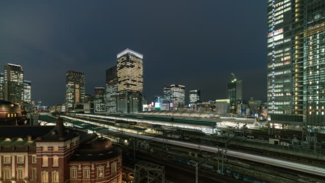 time lapse of tokyo station with various building cityscape and traffic road in tokyo, japan - tokyo japan stock videos & royalty-free footage
