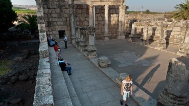 vídeos y material grabado en eventos de stock de time lapse of tour groups sitting and moving around synagogue ruins - plano de grúa
