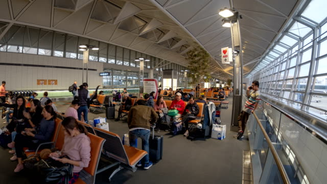 4k time lapse of tourist crowded waiting for boarding at airport boarding room - crowded airport stock videos & royalty-free footage