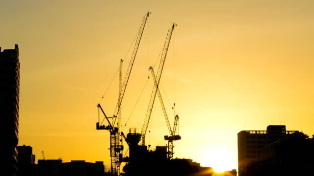time lapse of tower cranes on a sunset background - lyftkran bildbanksvideor och videomaterial från bakom kulisserna