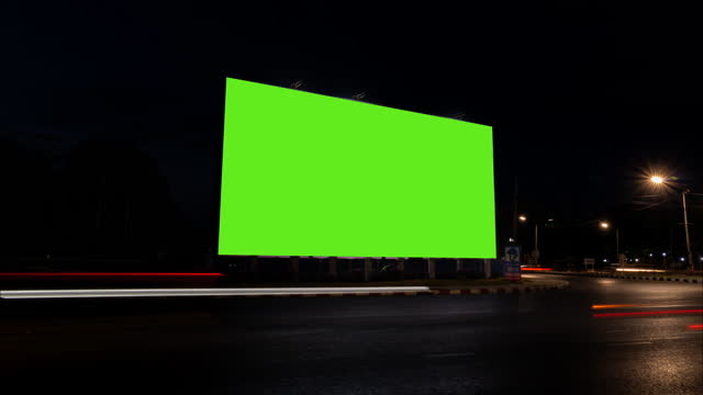 vídeos de stock e filmes b-roll de time lapse of traffic at night with blank advertising billboard green screen. - billboard