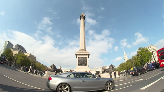 time lapse of traffic going by nelson's column, shot through fish-eye lens, london, england - nelson's column stock videos and b-roll footage