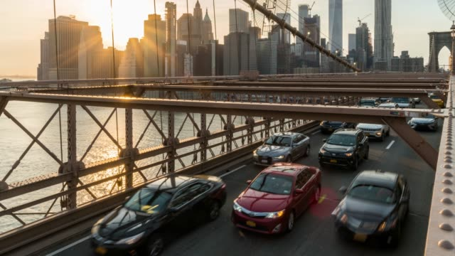4k time lapse of traffic in rush hour after working day on the brooklyn bridge over new york cityscape background with sunset, midtown manhattan, usa, united states, business and transportation concept - manhattan bridge stock videos and b-roll footage