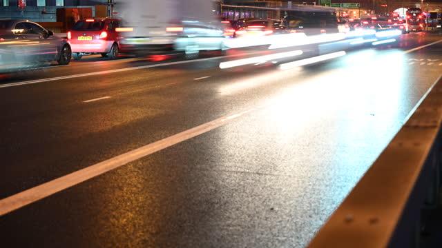 time lapse of traffic moving through urban london at night - traffic stock videos & royalty-free footage