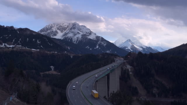 time lapse of traffic on brenner highway with europa bridge. cloudy sky and snow covered mountains in springtime. - brennero stock videos and b-roll footage