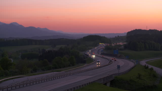 Time Lapse of traffic on motorway A8 at sunset. Upper Bavaria, Bavaria, Germany, Europe.