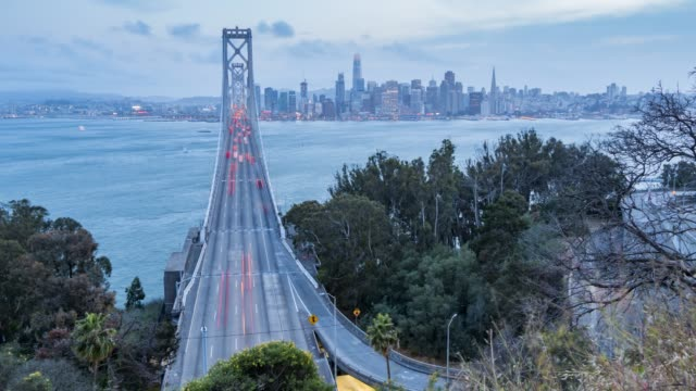 vídeos y material grabado en eventos de stock de time lapse of traffic on oakland bay bridge from yerba buena island at dusk, san francisco, california, usa, north america - puente colgante