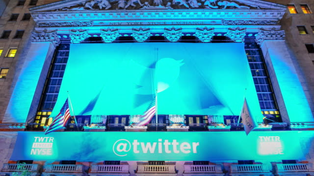 time lapse of twitter inc ipo logo banner hangs outside the new york stock exchange / wall street financial district new york city lower manhattan... - messaggistica online video stock e b–roll