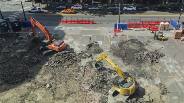 Time lapse of two excavators loosening earth at an early stage construction site in an urban setting