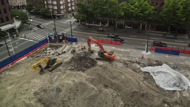 Time lapse of two excavators loosening earth at an early stage construction site in an urban setting on an overcast day