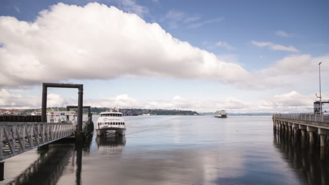 W/S time lapse of two ferries approaching the docks on a mostly sunny summer day with low clouds