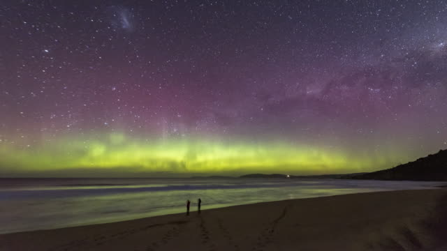 time lapse of two people dancing under the aurora australis or southern lights on a beach with bioluminescence in the waves. - aurora australis stock videos & royalty-free footage