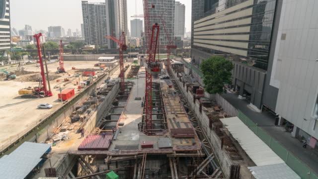 vidéos et rushes de laps de temps de 4k d'en construction, grues construit le bâtiment et les wokers travaillant à downtownn de bangkok en temps après-midi - grue engin de chantier