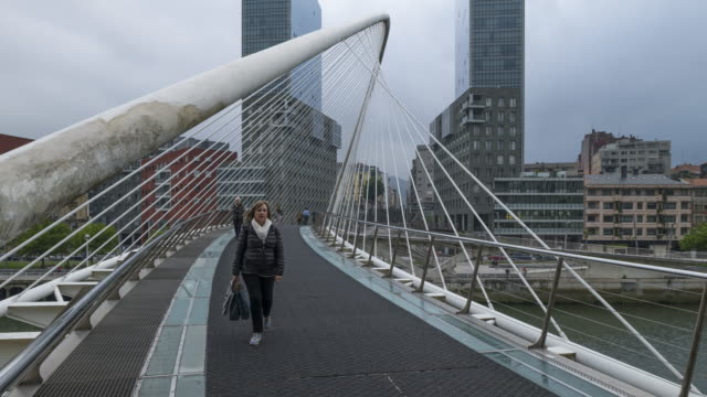 time lapse of walking people on zubizuri bridge in bilbao over nervion river. bilbao, nervion river, basque country, biscay, vizcaya province, spain, europe. - swing bridge stock videos & royalty-free footage