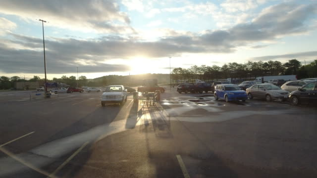 time lapse of walmart super shopping center parking lot at sunrise and customer came early during the 2020 global coronavirus pandemic ( no audio ) - moving past stock videos & royalty-free footage
