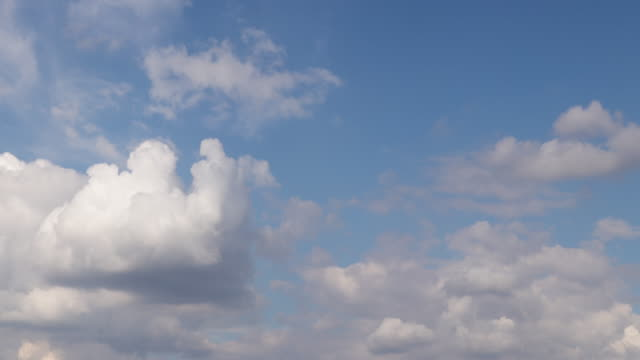 vidéos et rushes de time lapse of white clouds forming and billowing in a blue sky - ciel