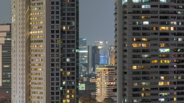 time lapse of windows light apartment and office buildings day to night - facciata video stock e b–roll