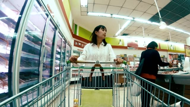 4k time lapse of woman with shopping cart in supermarket - wide shot stock videos & royalty-free footage