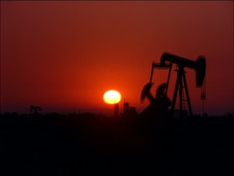 time lapse oil pump with sunrise in background / texas - 石油産業点の映像素材/bロール