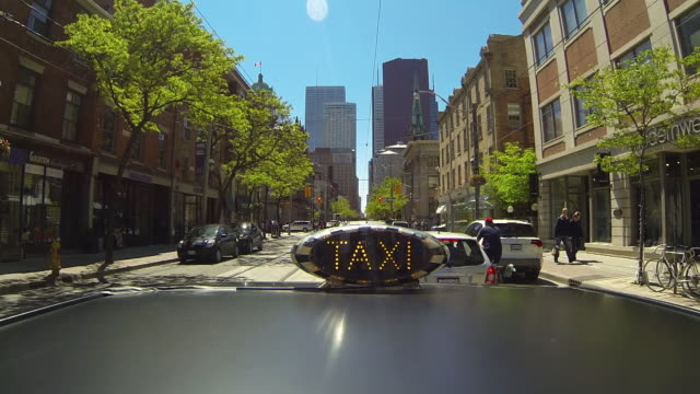 Time lapse on the top of a Taxi  forward Point of View.  The taxi drives into Toronto's financial district.  The TAXI sign is illuminated.