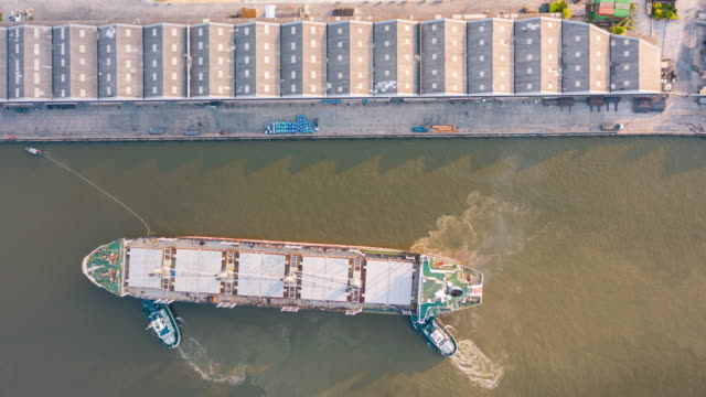 4k time lapse or hyper lapse : aerial top view tugboat pulling container cargo ship to loading dock at terminal commercial port for business logistics, import export, shipping or transportation. - tug boat stock videos & royalty-free footage
