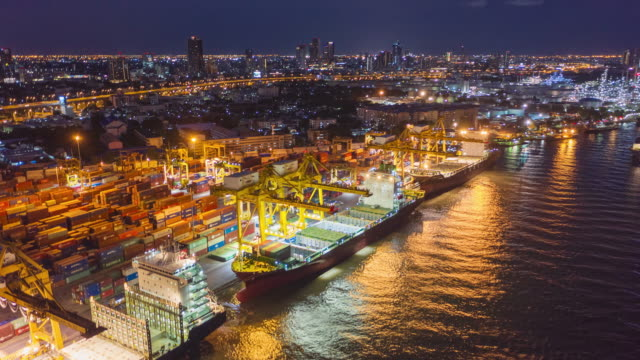 4k time lapse or hyper lapse : aerial view container cargo ship at terminal commercial port and working crane bridge loading container at night for business logistics, import export, shipping or freight transportation. - moored stock videos & royalty-free footage